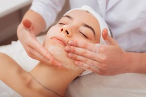 Why is exfoliation important? It helps clear dry skin and hydrate the underlying areas. A woman receives a facial in a massage session.