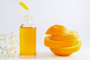 Vitamin c in skin care can stave off many diseases. A vial of oramge extract next to a sliced orange.